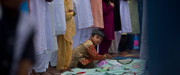 A child looks as Indian Muslims offer Eid al-Fitr prayers at a playground in Guwahati, India, on Wednesday, June 5, 2019. Credit: AP